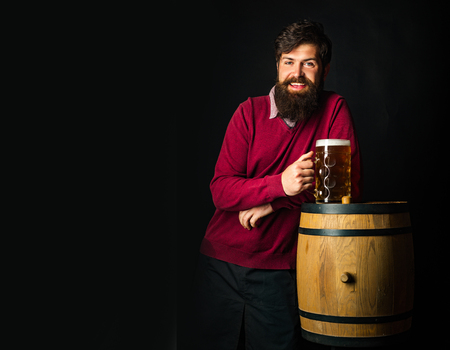 Bearded man drinking lager beer. Beer in Germany. Portrait of handsome young man tasting a draft beer. Wooden barrel and glass of beer. Stock Photo