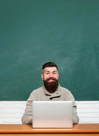 Teacher job - profession and learning concept. Teacher teaches a student. School day. Tutoring. Young female student ready to write exam testing. Blackboard for text, copy space.