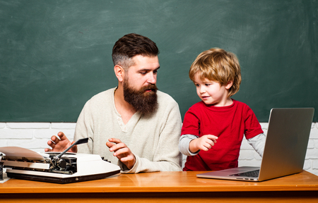 Concept of education and teaching. Teacher helping pupils studying on desks in classroom. Copy space. Elementary school. Young or adult. Dad son are concentrated on the problem. Фото со стока