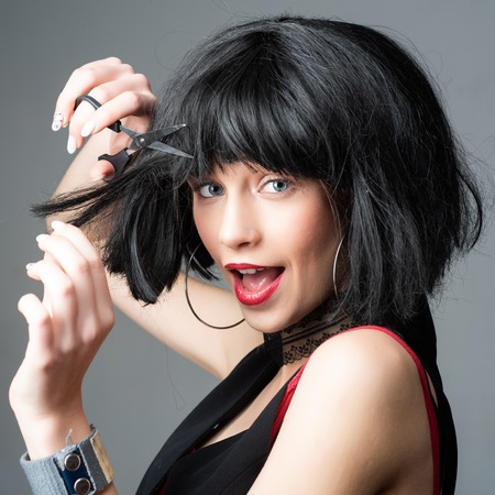 crazy girl with funny brunette hairdo. woman cut hair with scissors. hairdresser salon. Sexy girl. Sensual woman. makeup and hair style. trendy look. Beauty and fashion. Woman with brittle hair. wig
