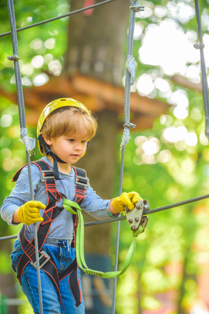 Every childhood matters. Kid climbing trees in park. High ropes walk. Cute child in climbing safety equipment in a tree house or in a rope park climbs the rope Banque d'images - 122567711