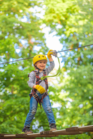 Beautiful little child climbing and having fun in adventure Park. Hiking in the rope park girl in safety equipment.