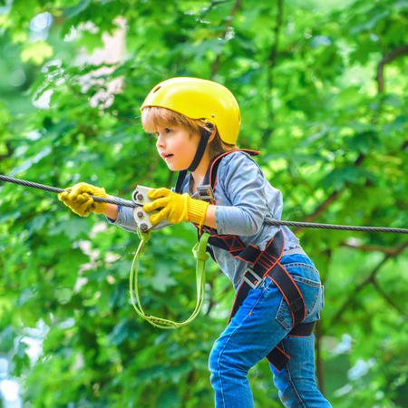 Child. Helmet and safety equipment. Hiking in the rope park girl in safety equipment. Toddler kindergarten. Early childhood development