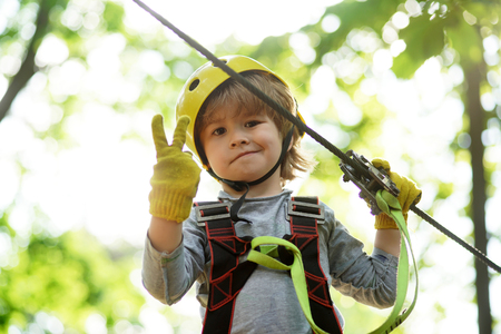 Children summer activities. Kid climbing trees in park. Children fun. Cute baby boy playing. Every childhood matters.