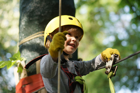 Happy child boy calling while climbing high tree and ropes. Happy little child climbing on a rope playground outdoor. Hike and kids concept. Stock Photo