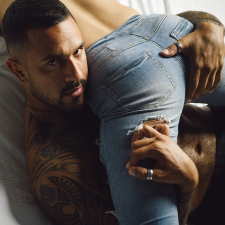 Muscular latino man hold female ass. Female butt in his arms. Buttocks in denim pants. Stok Fotoğraf
