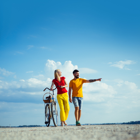 Sexy couple. Married couple and problems concept. Lovers having romantic moments. I love you very much. Summer woman with retro bike on blue sky background. Copy space.