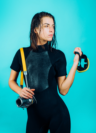 Dive deep. Sensual woman with scuba gear and dive equipment. Sexy diver with wet hair holding dive mask and camera for underwater shooting. We dive 360 days a year