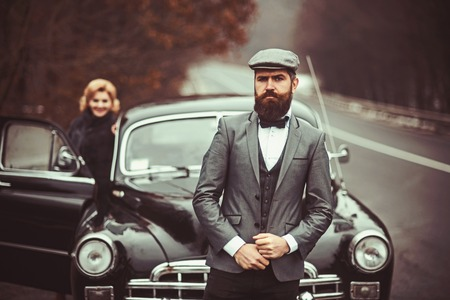 Escort of girl by security. Retro collection car and auto repair by mechanic driver. Travel and business trip or hitch hiking. Couple in love on romantic date. Bearded man and sexy woman in fur coat.