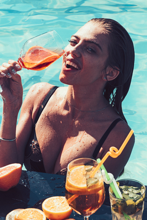 Drink fresh vitamin juice, diet. woman drinking cocktail in swimming pool. 写真素材