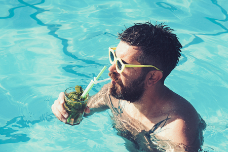 Summer vacation at Miami beach or Maldives. Pool party with hipster in blue water. Cocktail party with bearded man in pool. Relax at sea and spa resort. Man swimming and drink alcoholic mojito