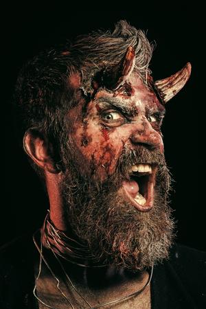 Halloween-Mann-Teufelsschrei mit Wut auf schwarzem Hintergrund Standard-Bild