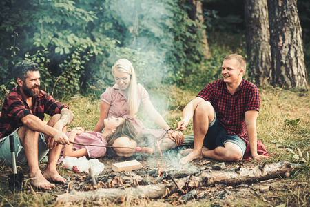 Grilling sausages over campfire, campers roasting sausages on toasting sticks. Fire place with friends or tourists are sitting near flame