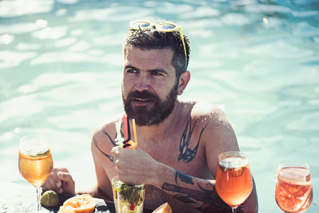 Cocktail party with bearded man in pool. cocktails in pool bar near bearded man.