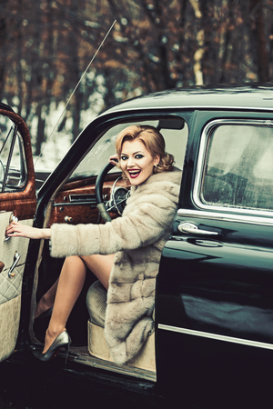 Retro car and sexy woman in fur coat. Retro collection car and auto repair by driver