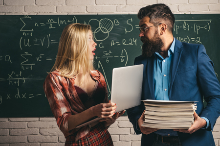 Couple of pretty sexy girl student holding heap of books and handsome bearded man teacher or professor on classroom background. Female student with a male teacher in classroom.