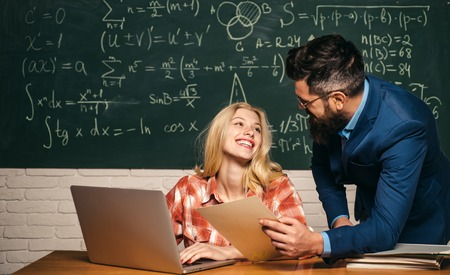 Studying at university. Student Studying Hard Exam. Education and learning people concept - female student and Teacher. Tutoring. Concentrated students following explanations of teacher in class. Standard-Bild