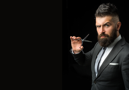 Confident barber at barbershop. Barber and hairdresser salon. Beard care, perfect beard. Bearded man in formal business suit. Brutal male hipster cut hair with hairdressing scissors - copy space 스톡 콘텐츠