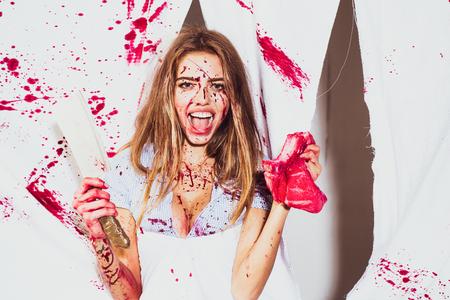Sale de sang, une femme tient dans sa main un couperet sanglant sur fond blanc en studio. Jeune fille de boucher tenant un morceau de viande crue et un couperet isolé sur fond blanc sanglant. Banque d'images