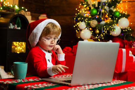 Christmas shopping concept. Gifts service. Santa little helper. Smart toddler surfing internet. Little boy santa hat and costume. Boy child with laptop near christmas tree. Buy christmas gifts online