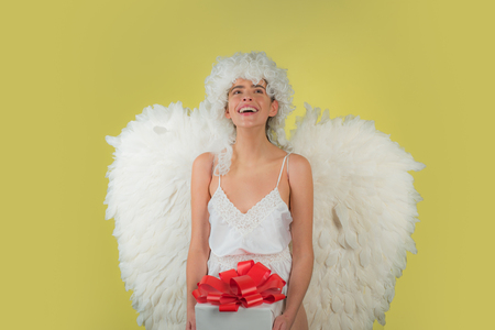 Beautiful fairy flying girl in white dress. Beautiful woman posing with angel wings. Long white wings. Romantic young beauty as an angel.