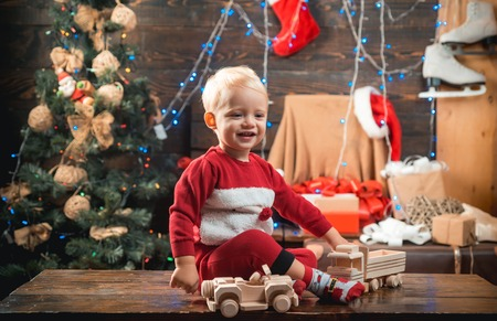 Portrait kid with gift on wooden background. Christmas kids - happiness concept. Cute little child girl is decorating the Christmas tree indoors. Smiling child peeping from behind Christmas tree in li