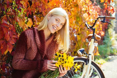 Jesienny bukiet. Ciepła jesień. Dziewczyna z rowerem i kwiatami. Kobieta rower jesień ogród. Aktywny wypoczynek i styl życia. Jesienne proste przyjemności. Dziewczyna jeździć na rowerze dla zabawy. Blondynka lubi relaks w parku? Zdjęcie Seryjne