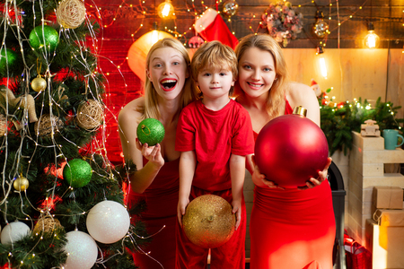 Women red dresses celebrate christmas with little cute baby. Family bonds. Love peace joy. Kid boy with mom or aunts sisters having fun. Join celebration. Christmas family fun. Christmas party Archivio Fotografico - 123083818