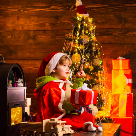 Best wishes. Family holiday. Christmas gift. Cute little child boy play near christmas tree. Kid enjoy winter holiday at home. Home filled with joy and love. Merry christmas and happy new year