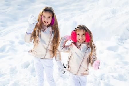 Deux petite fille jouant sur la neige en hiver. Bataille de boules de neige. Enfants d'hiver s'amusant à jouer dans la neige à l'extérieur. Les enfants lancent une boule de neige. Banque d'images