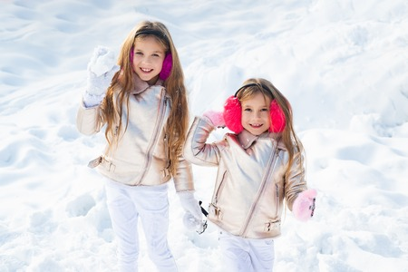 Two little girl playing on snow in winter time. Snowball fight. Winter kids having fun playing in snow outdoors. Kids throwing a snowball.