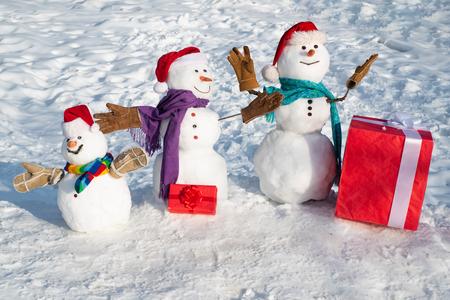 Aufgeregte Schneemann-Familie mit einer Tüte Geschenke. Familie Schneemann auf den Hintergrundschneeflocken. Winterhintergrund mit Schneeflocken und Schneemann. Familie der Schneemänner.