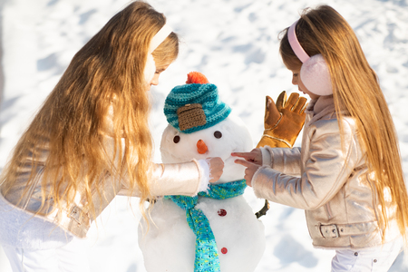Happy child plaing with a snowman on a snowy winter walk. Making snowman and winter fun for children. Two little girl playing on snow in winter time.