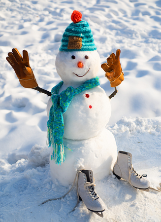 The snowman is wearing a fur hat and scarf. Christmas snowman close up with scarf. Funny snowman in stylish hat and scarf on snowy field. Snow men.