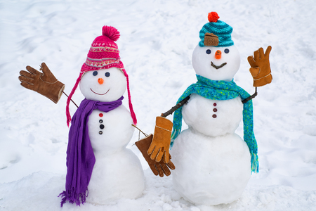 A loving couple of snowmen. Christmas background with couple of snowman. Snowman couple outdoor. Cute snow man in hat and scarf on snowy field. Funny snowmen. Festive Art Greeting Card.