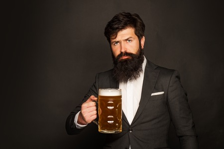 Portrait of handsome young man tasting a draft beer. Man holds glass of beer. Handsome bearded man drinking beer.