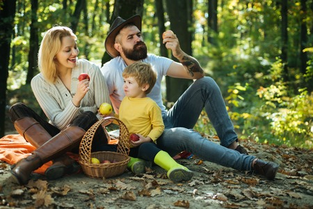 Happy family with kid relaxing while hiking in forest. Basket picnic healthy food snacks fruits. Mother father and small son picnic. Picnic in nature. United with nature. Family day concept