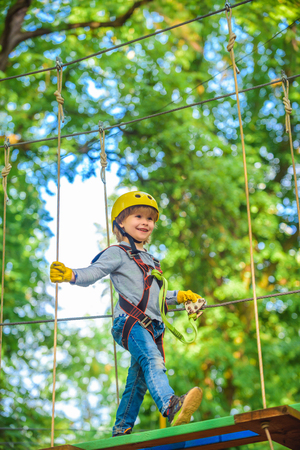 Happy child climbing in the trees. Balance beam and rope bridges. Roping park. Climber child on training. Rope park - climbing center. Child playing on the playground. Toddler age.