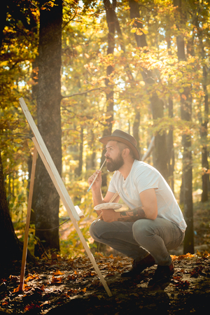 Capture moment. Bearded man painter looking for inspiration autumn nature. Drawing from life. Painter artist forest. Art concept. Painting in nature. Start new picture. Painter with easel and canvas Imagens