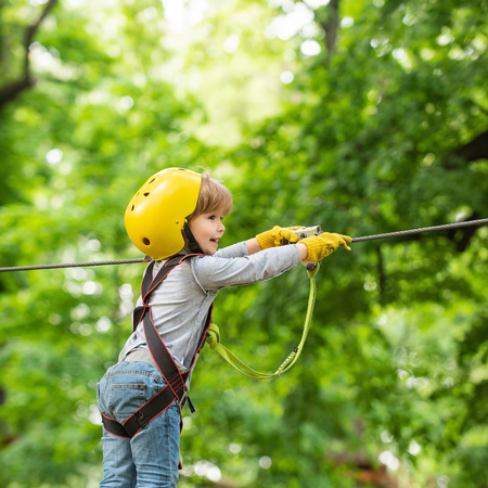 High ropes walk. Child. Kid climbing trees in park. Eco Resort Activities. Hike and kids concept. Helmet and safety equipment Stock Photo