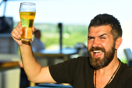 Handsome barman holding a pint of beer. Man holds glass of beer. Enjoy in pub. Beer time.