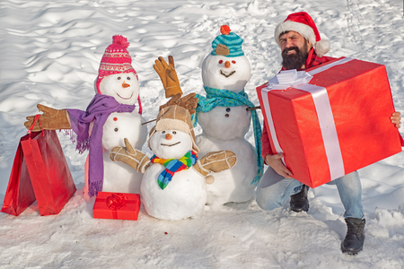 Delivery gifts. Happy winter snowman family. Mother snow-woman, father snow-man and kid wishes merry Christmas and Happy New Year. Cute snowman at a snowy village. Stockfoto