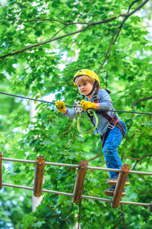 Rope park - climbing center. Carefree childhood. Little child climbing in adventure activity park with helmet and safety equipment. Roping park