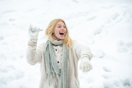 Young american woman throwing snowball at sunny day in the winter park. Girl playing with snow in park in America. Women woman. Winter emotion. Stock Photo