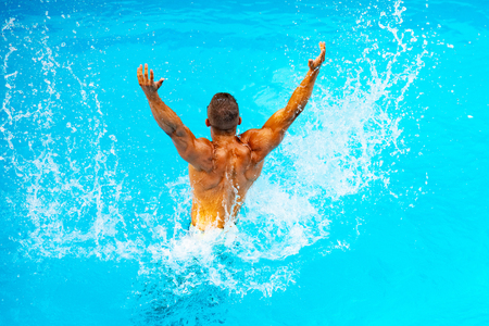 Perfect male Torso on blue water background. Vacation at Paradise. Vacation. Luxury Travel Expert. Young man Swimming Pool Concept. Relaxed on Bahamas or Bermuda - traveling concept.