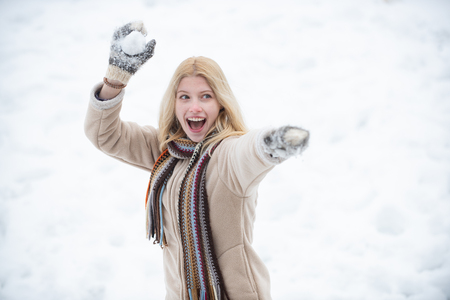 Snowball fight. Woman holding the snowball in hands. Models having fun in winter park. Happy woman winter portrait. Winter emotion.