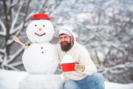 Winter chef cook. Bearded chef with snowman cook at sunny day in the winter park. Funny winter Greeting Card with snow man. Funny kitchen.