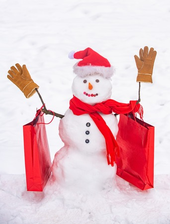 Cute snowman at a snowy village. Greeting snowman. Handmade snowman in the snow outdoor. Snowman gentleman in winter hat.