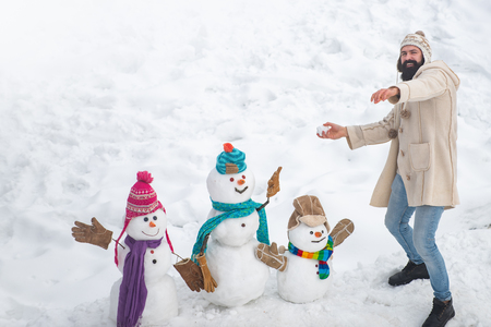 Happy winter snowman family. Happy snow man and bearded man on sunny winter day. Mother snow-woman, father snow-man and kid wishes merry Christmas and Happy New Year. Imagens
