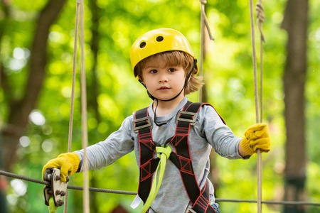 Child playing on the playground. Happy little child climbing on a rope playground outdoor. Adventure climbing high wire park. Cute baby boy playing